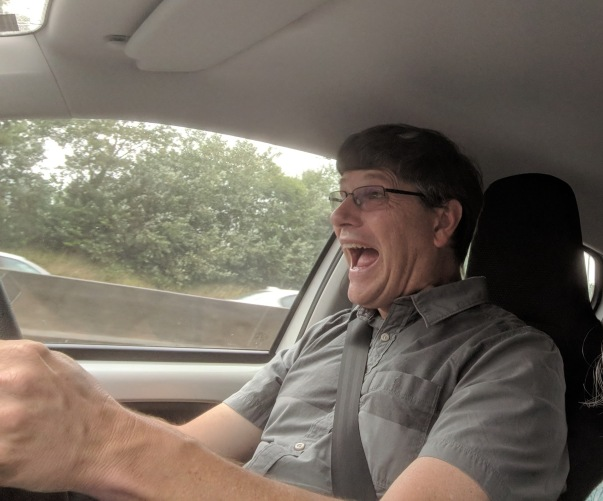 Bill is learning how to drive on the right side of the car and the left side of the road. Weird!